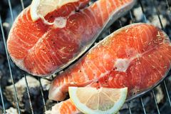 Salmon on grill. Salmon preparation process on wooden grill. Grilled fish steaks on fire. Top view stock images