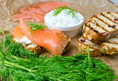 Salmon on a grilled bread. With yogurt cucumber salad on wooden background stock photos