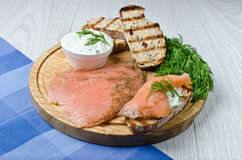 Salmon on a grilled bread. With yogurt cucumber salad on wooden background stock image