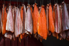 Salmon hanging in an ordered pattern for smoking Stock Photos