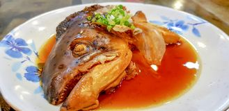 Salmon head boiled with soy sauce. A famous traditional Japanese food. Salmon head boiled with soy sauce in the Japanese style dish garnish with mince spring Royalty Free Stock Photos