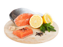 Salmon with herbs and lemon slices on cutting board. Isolated on white background Stock Photography