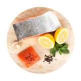 Salmon with herbs and lemon slices on cutting board. Isolated on white background Stock Images