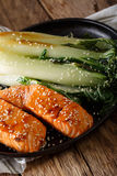 Salmon in honey-soy glaze and fried bok choy close-up. vertical Stock Image