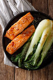 Salmon in honey-soy glaze and fried bok choy close-up. Vertical Stock Images