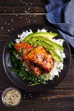Salmon in honey-soy glaze with rice, spinach and avocado. stock image