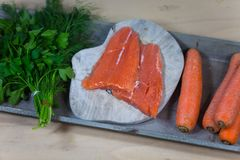 Salmon with ingredients, carrots, dill, parsley on tray. Gourmet Royalty Free Stock Photo