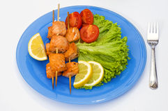 Salmon kebab with lettuce, lemon and cherry on blue plate Stock Photos