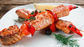 Salmon kebab on wooden table. Japanese seafood. Appetizing salmon with tomatoes and chili pepper decorated with lemon on white plate, close up view. Japanese Stock Photos