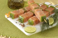 Salmon kebabs. Elegantly displayed with lime and herbs Royalty Free Stock Images