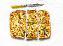 Salmon, leek, spinach, cheese puff pastry tart, pie on light background royalty free stock photo