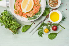 Salmon with lemon, oil and fresh seasoning in white pan on rustic wooden background Stock Photos