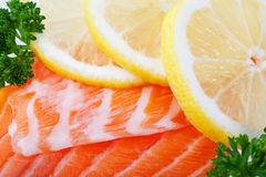 Salmon With Lemon Slices. Fillets of fresh salmon with lemon slices  on ice.  Macro Stock Photo
