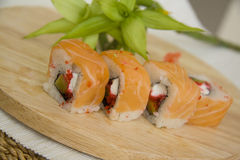 Salmon maki on plate with bamboo green Royalty Free Stock Images