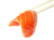 Salmon meat in chopsticks. A piece of raw salmon meat in two wooden chopsticks isolated over white background Royalty Free Stock Photography