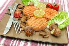 Salmon medallion, stuffed snails and mushrooms on a plate Royalty Free Stock Photography