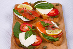 Salmon, Mozzarella, Tomatoes, Lemon, Capers and Pesto Sauce Bruschetta. Royalty Free Stock Image