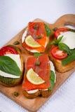 Salmon, Mozzarella, Tomatoes, Lemon, Capers and Pesto Sauce Bruschetta. Stock Photo