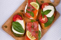 Salmon, Mozzarella, Tomatoes, Lemon, Capers and Pesto Sauce Bruschetta. Stock Photography