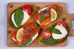 Salmon, Mozzarella, Tomatoes, Lemon, Capers and Pesto Sauce Bruschetta. Stock Image