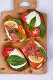 Salmon, Mozzarella, Tomatoes, Lemon, Capers and Pesto Sauce Bruschetta. Royalty Free Stock Photos