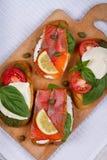 Salmon, Mozzarella, Tomatoes, Lemon, Capers and Pesto Sauce Bruschetta. Stock Images