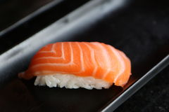 Salmon nigiri. One salmon nigiri on a black plate Royalty Free Stock Photos