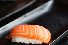 Salmon nigiri. One salmon nigiri in focus on black plate Royalty Free Stock Photography