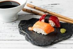 Salmon Nigiri. Smoked salmon Nigiri with wasabi paste and red tuna nigiri on slate stone. Chopsticks and bowl with soy sauce in the background on old white wood royalty free stock photo