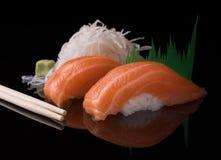 Salmon Nigiri Sushi Dos pedazos de sushi de color salmón japonés en una superficie reflexiva negra sirvieron con wasabi y el rába Imagen de archivo
