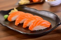 Salmon nigiri sushi plate. Salmon nigiri sushi foursome on black dishes in restaurant table Stock Photos