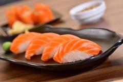Salmon nigiri sushi plate. Salmon nigiri sushi foursome on black dishes in restaurant table Royalty Free Stock Photography