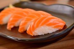 Salmon nigiri sushi plate. Salmon nigiri sushi foursome on black dishes in restaurant table Royalty Free Stock Photos