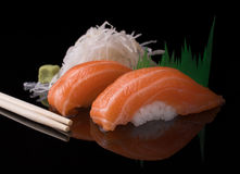 Salmon nigiri sushi. Two pieces of Japanese salmon sushi on a black reflective surface served with wasabi and white radish. Two pieces of Japanese salmon sushi stock image