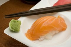 Salmon nigiri sushi on white plate. Salmon sushi on white plate with wasabi and chopsticks stock images