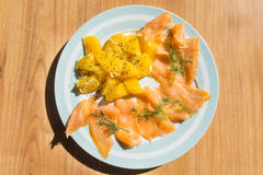 Salmon with orange salad. On the wood table Royalty Free Stock Photo