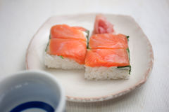 Salmon oshizushi and sake Stock Photos