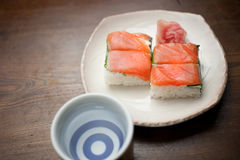 Salmon oshizushi and sake Stock Image