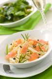 Salmon Pasta. Smoked Salmon Penne (tube-shaped pasta) with cappers, tarragon and cheese creamy sauce. Caesar salad and glass of white wine out of focus. Shallow Stock Photos