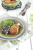 Salmon patties. With creamy mushrooms and rocket salad on green plate and rustic wooden table with green saucepan and cast iron trivet royalty free stock photos
