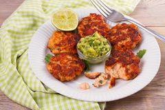 Salmon patties or cakes, lime and avocado on white plate. Fritters of fish. Salmon burgers stock photography