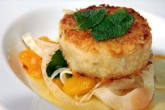 Salmon patty. Over mandarin oranges Royalty Free Stock Images