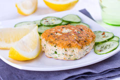 Salmon patty. Close up of a salmon patty served woth cucumber and lemon Royalty Free Stock Image