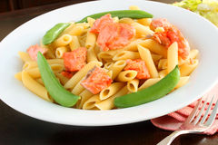Salmon with penne and sugar snap peas Stock Photos