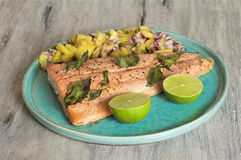Salmon with pineapple salsa and lime stock image