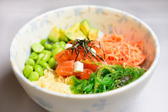 Salmon poke bowl. Japanese poke bowl served with rice, salmon, edamame krab, avocado, creamcheese Stock Image