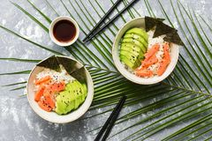 Salmon poke bowl with rice,nori, avocado , black sesame seeds on a gray background decorated with tropical leaves. Top view, flat