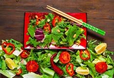 Salmon Poke Salad op rode plaat met eetstokjes op Organische Textuur van Saladebladeren op Houten Achtergrond, smakelijke en gezo stock afbeelding