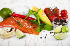 Salmon. Portion of fresh salmon fillet with vegetables, aromatic spices and herbs on a wooden background Royalty Free Stock Image