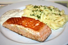 Salmon with potato salad. On the white plate royalty free stock images